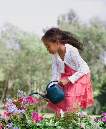Cute young black girl watering flowers