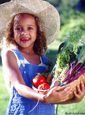 Child with Fresh Vegetables in the Garden