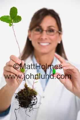 Female scientist holding plant and medication