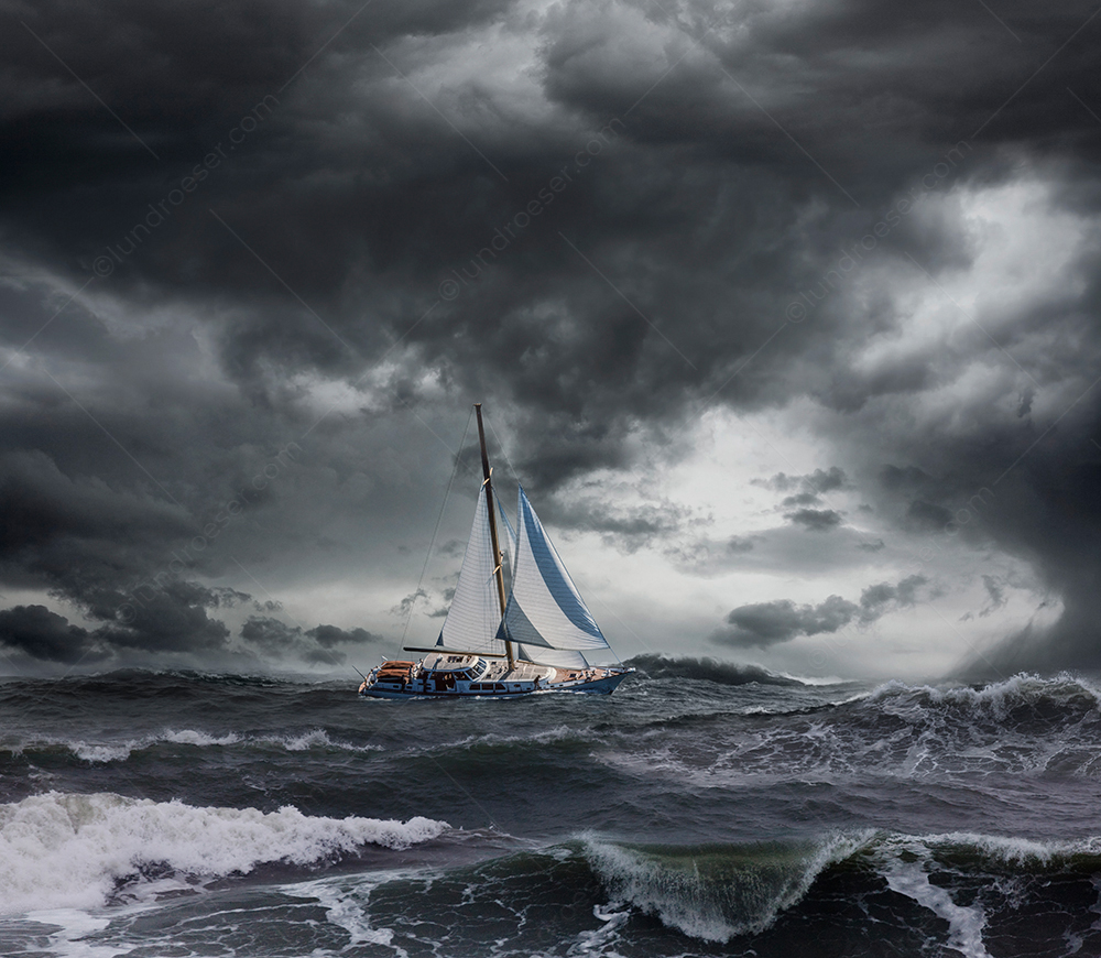 A sailboat crests a wave in an ocean storm in a stock photo about challenge, risk, and sailing.