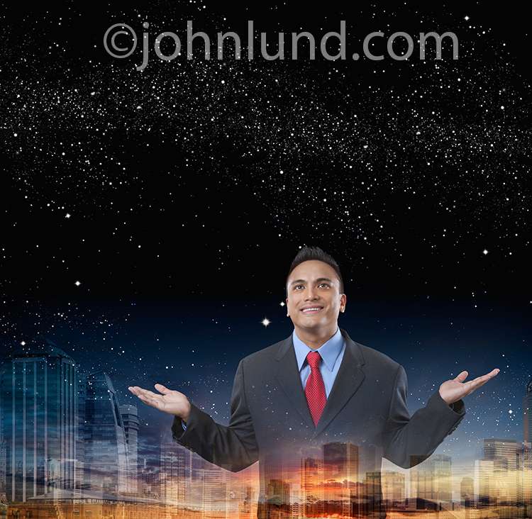 An Hispanic Businessman opens up his arms to the night sky with a city in the background