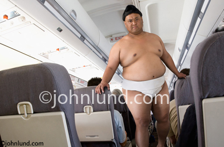A Sumo Wrestler walks down the Aisle of a Commercial airliner