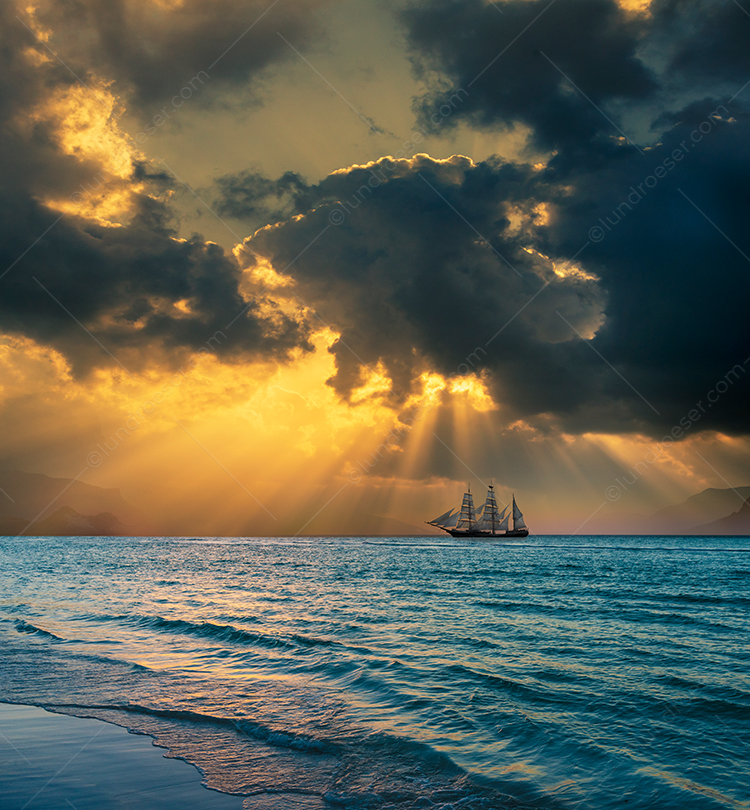 Tall Ship Sailing Under God Ray Sunset