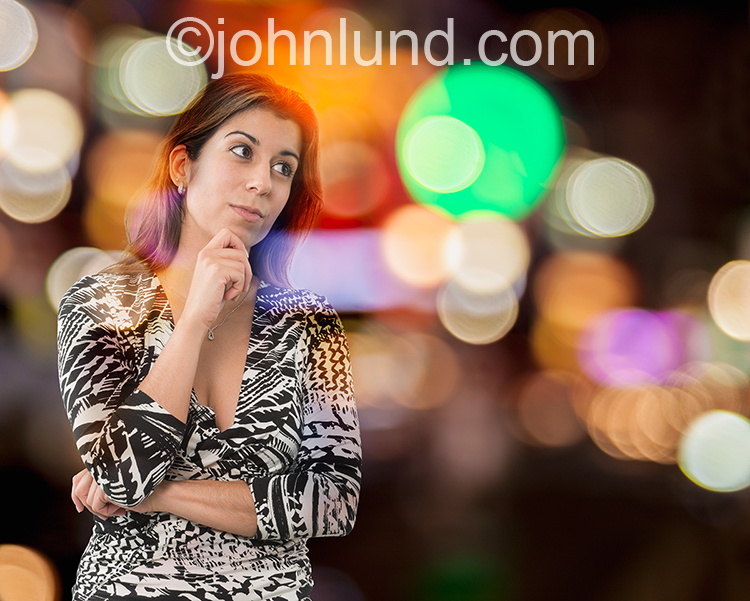 Woman Contemplating Business Against Colored Lights