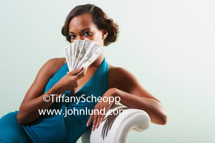 Woman Peering Over a Handful of Cash